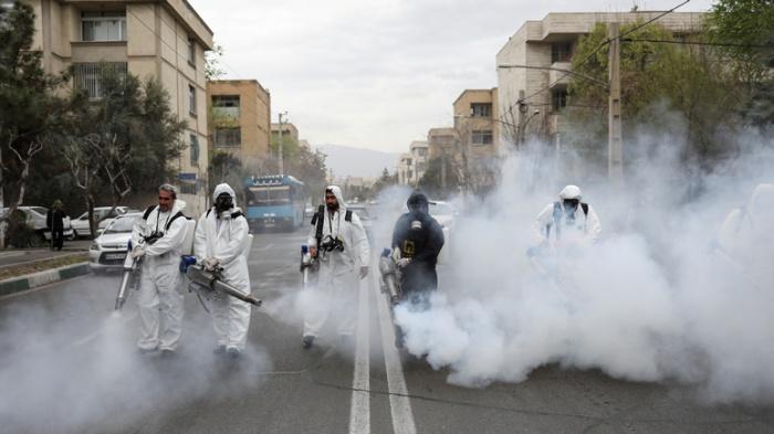 Сотрудники специальных служб дезинфицируют улицы Тегерана.